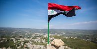 Syrian state flag fluttering above the Krak des Chevaliers castle in Syria