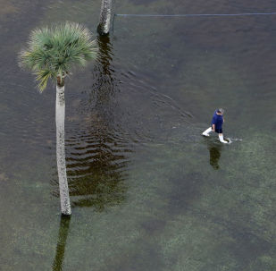 Мужчина идет по затопленной парковке в США