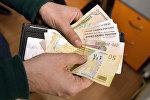 Мужчина пересчитывает полученные деньги, фото из архива
