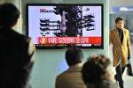 Туристы на железнодорожном вокзале в Сеуле смотрят новость о запуске ракеты