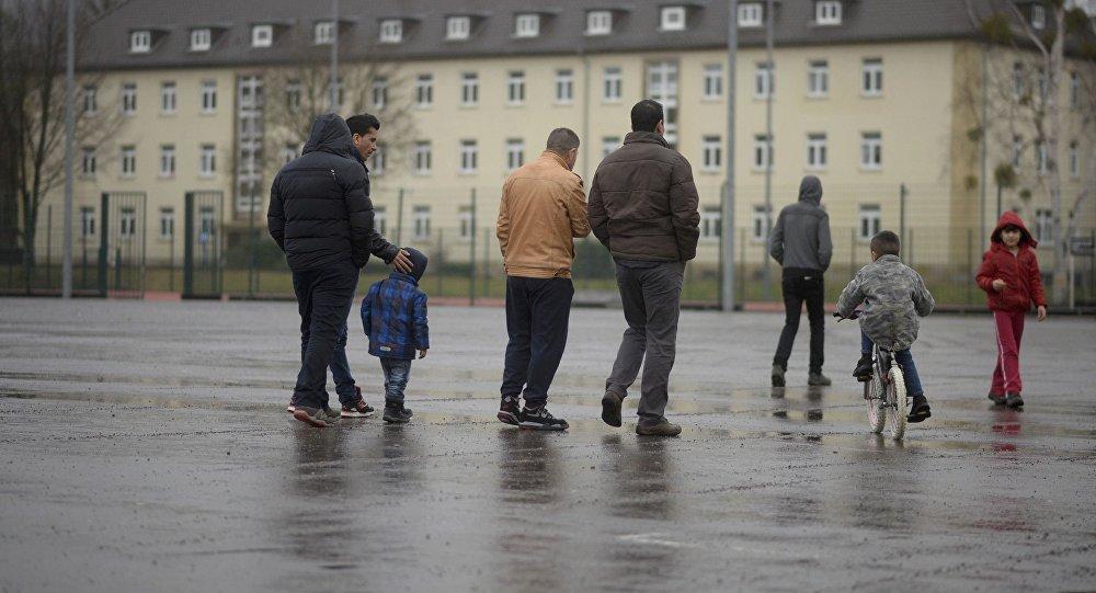 Мигранты и их дети гуляют на территории лагеря для беженцев в Гамельне, Нижняя Саксония