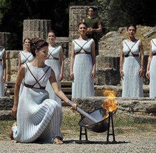 Греческая актриса Катерина Леху, играющая роль верховной жрицы, зажигает факел от солнечных лучей, отраженных в параболическом зеркале