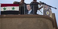 Солдаты сирийской армии рядом с фотографией президента Башара Асада в городе Эт-Талль, Сирия. Архивное фото