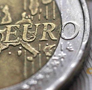 Монета достоинством в 1 евро на купюре номиналом в 10 фунтов стерлингов