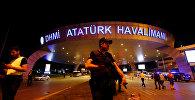 Полицейский стоит на страже у входа в аэропорт имени Ататюрка в Стамбуле, Турция, после теракта