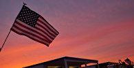 Женщина фотографирует американский флаг во время празднования Дня независимости США в Атлантик-Бич