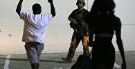 Чернокожий мужчина поднимает руки перед сотрудником правоохранительных органов Далласа