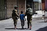 Израильские солдаты арестовывают палестинского мальчика после столкновений в центре города на Западном берегу Хеврон. 20 июня 2014 года