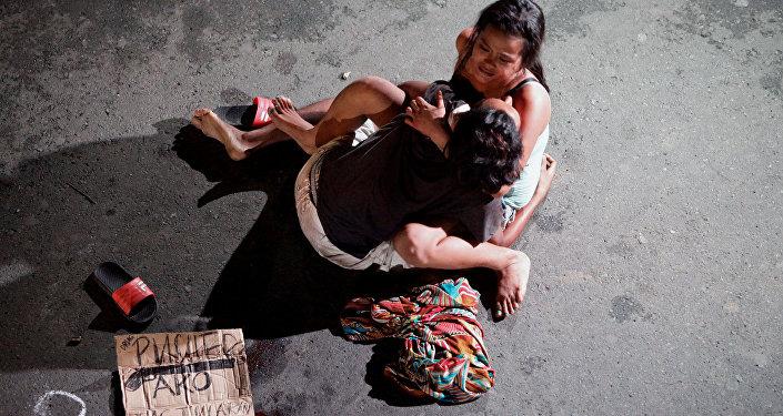 Девушка обнимает тело своего партнера, который был убит на улице бригадой дружинников. Филиппины, Манила. 23 июля 2016 года