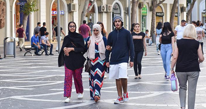 Молодая арабская пара на Торговой улице в Баку