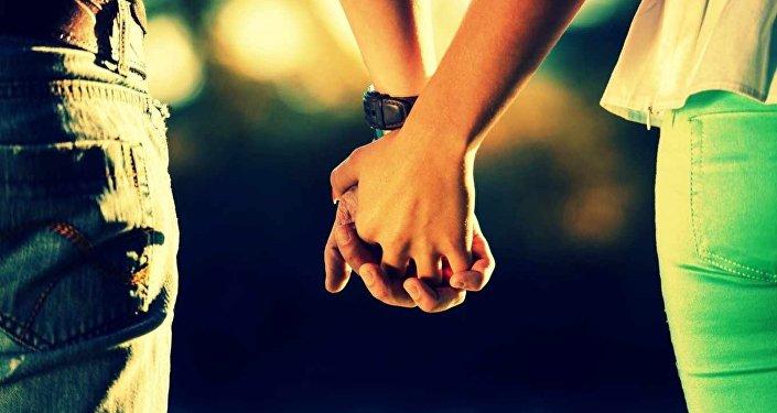 Парень с девушкой держатся за руки. Архивное фото
