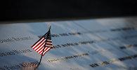 Флаг США на доске с именами жертв теракта в Национальном мемориале 11 сентября. Манхэттен, Нью-Йорк, 10 сентября 2016 года