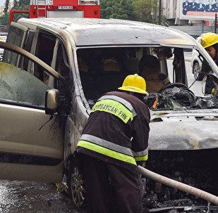 Сотрудник МЧС Азербайджана у сгоревшей в результате ДТП машины, фото из архива