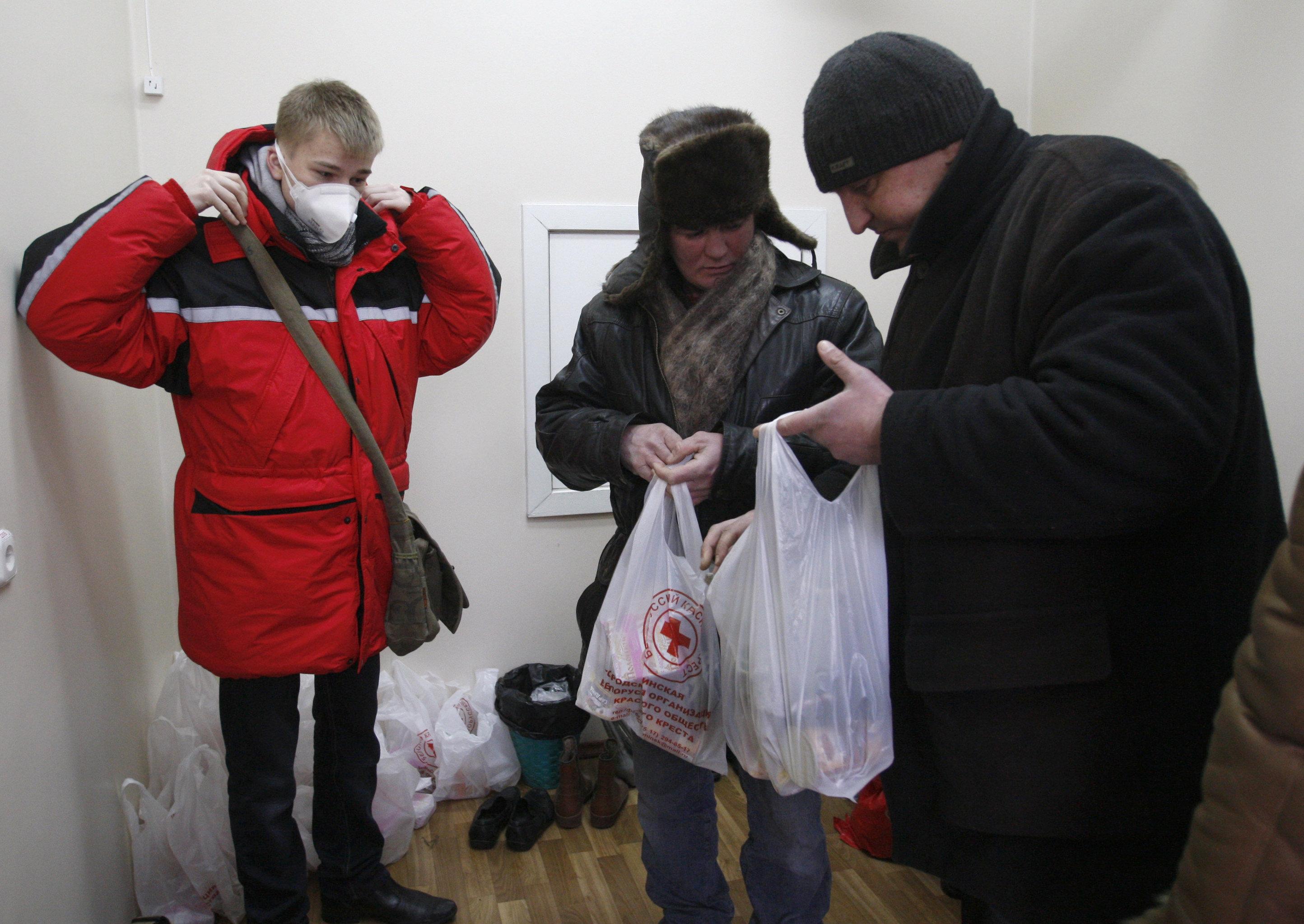 Сотрудники общественной организации Красный крест выдают людям без определенного места жительства одежду и еду в Центре дезинфекции и стерилизации в Минске во время акции, направленной на поддержку бездомных в холодное время года