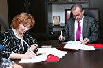 Генеральный директор интернет-медиахолдинга Pravda.Ru Инна Новикова и генеральный директор Vesti.Az Араз Зейналов подписывают соглашение