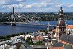 Колокольня Домского кафедрального собора (слева) и вантовый мост через реку Даугаву в Риге в Латвии