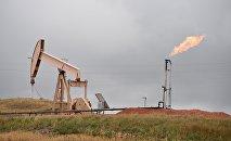 Нефтяной насос и газовый факел в городе Уиллистон, штат Северная Дакота, 6 сентября 2016 года