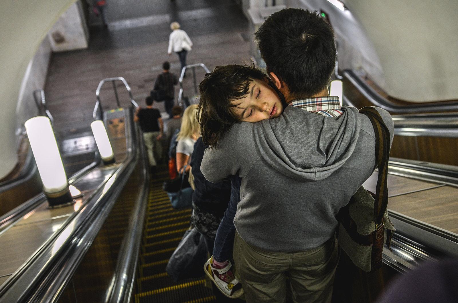 Moskva metropoliteninin eskalatorunda, atasının qucağında yuxuya getmiş uşaq