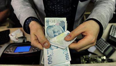 Сотрудник обменного пункта с турецкими банкнотами в руках, фото из архива