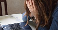 Девушка на рабочем месте закрывает лицо руками, фото из архива