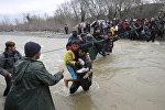 Беженцы переходят через реку вблизи греко-македонской границы, к западу от деревни Идомени, Греция, 14 марта 2016 года
