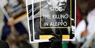 Женщина держит плакат во время акции протеста, призывая к прекращению насилия в Алеппо