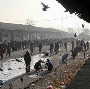 Мигранты стоят в очереди, чтобы получить бесплатную еду на ттерритории заброшенного таможенного склада в Белграде, Сербия, 21 декабря 2016 года