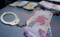 Наручники и пачки денег на столе, фото из архива