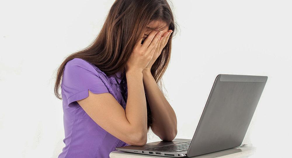 Молодая женщина сидит за компьютером, фото из архива