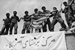 Люди с порванным флагом США стоят на крыше здания посольства Соединенных Штатов в ходе массовых антиамериканских демонстраций в Тегеране, 25 мая 1979 года