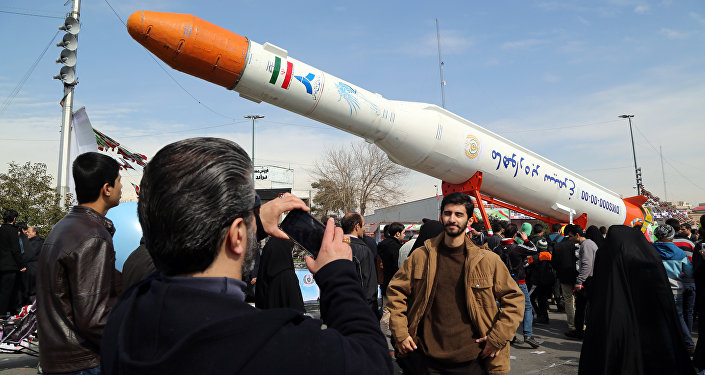 Люди фотографируются у ракеты-носителя Simorgh (Феникс) в день празднования 37-й годовщины Исламской революции, Тегеран, 11 февраля 2016 года