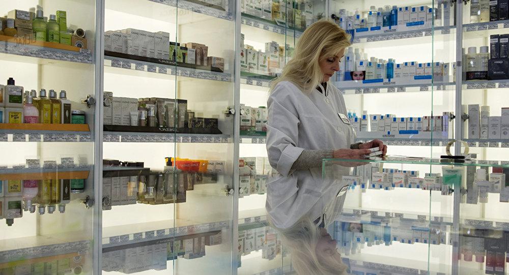 Сотрудница аптеки разбирает лекарства, фото из архива