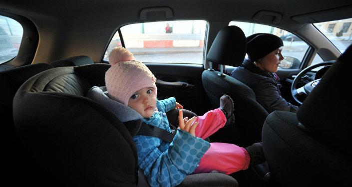 Avtomobildə xüsusi oturacaqda oturmuş uşaq
