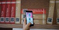 Девушка сканирует QR-код на презентации проекта Мобильные библиотеки, фото из архива