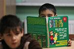 Ученики на уроке чтения в начальной общеобразовательной школе