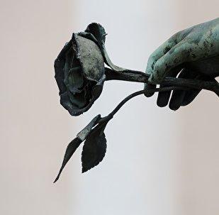 Памятник мужчине, держащему в руке розу, фото из архива