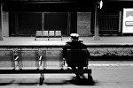 Пожилой мужчина, сидящий на скамье, фото из архива