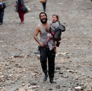 Мужчина с дочерью на руках бегут с подконтрольной Исламскому государству (ИГ, запрещена в РФ) территории Мосула