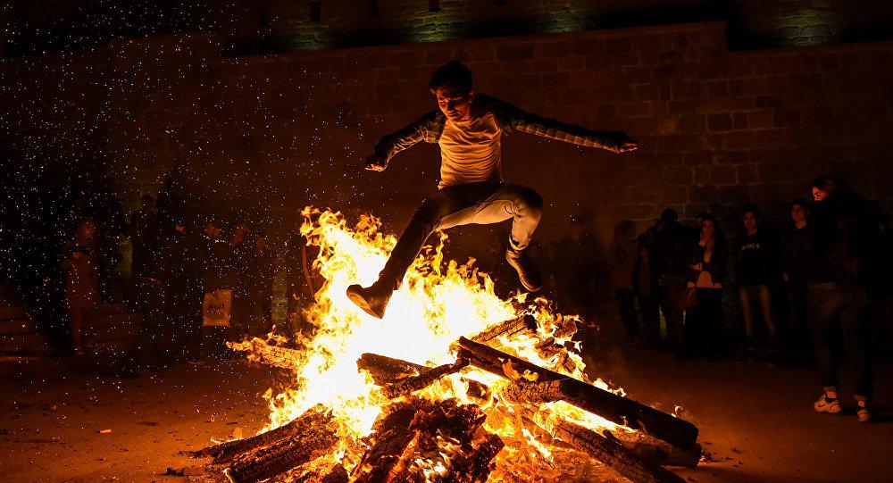 Мужчина прыгает через костер во время празднования вторника огня в Баку, фото из архива