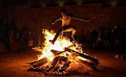 Мужчина прыгает через костер во время празднования вторника огня в Баку