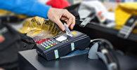 Оплата покупки на POS-терминале, фото из архива