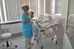 Сотрудница Детской клинической больницы с новорожденным, фото из архива