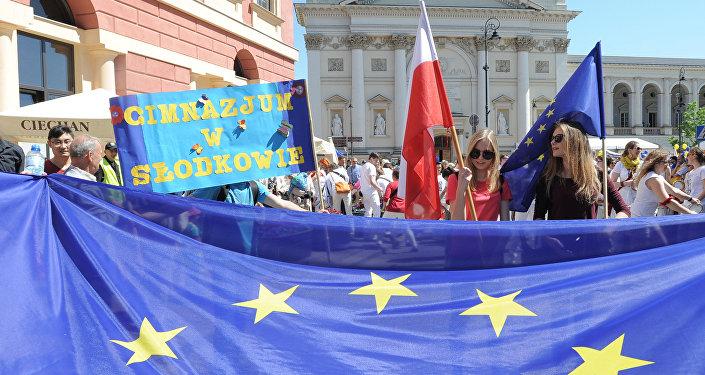 Девушки с флагами Евросоюза и Польши в ходе парада Шумана в Варшаве, 7 мая 2016 года