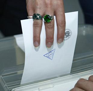 Избирательница опускает бюллетень в урну для голосования на выборах в Совет Старейшин на избирательном участке в Ереване