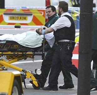 Сотрудники службы спасения оказывают помощь раненому в ходе перестрелки на Вестминстерском мосту в Лондоне, 22 марта 2017 года