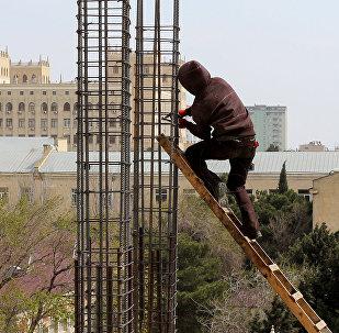 Рабочий на стройке многоэтажного дома, фото из архива