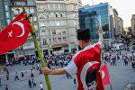 Мужчина с флагом на площади Таксим в Стамбуле