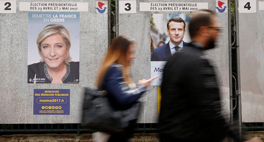 Люди проходят мимо агитационных плакатов лидера политической партии Марин Ле Пен, французского национального фронта и главы политического движения Эммануэля Макрона , фото из архива