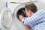 Мастер по ремонту бытовой техники осматривает стиральную машину, фото из архива