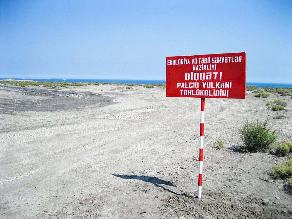 Текст на табличке: Министерство экологии и природных ресурсов. Внимание! Грязевой вулкан опасен!